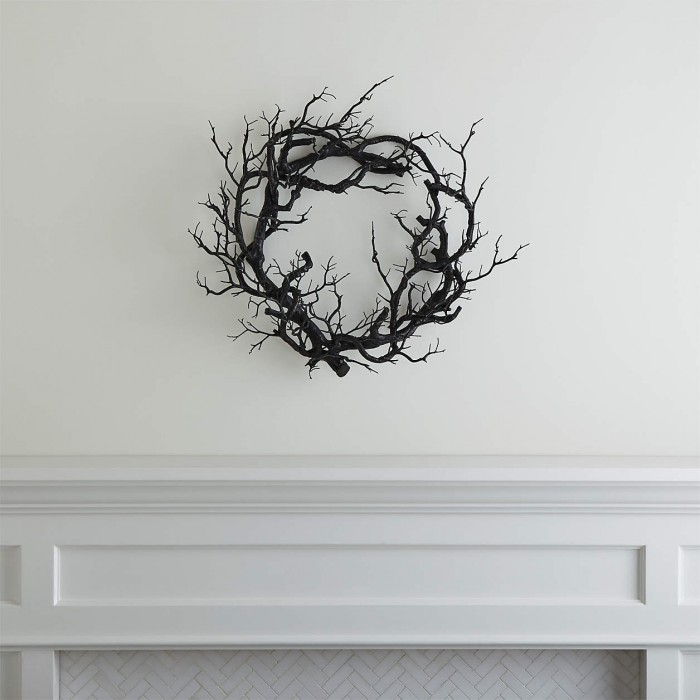 Black branch wreath on a white wall over a white mantle