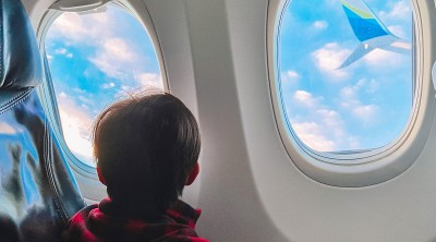 Child Flying on Airplane Looking Out Window