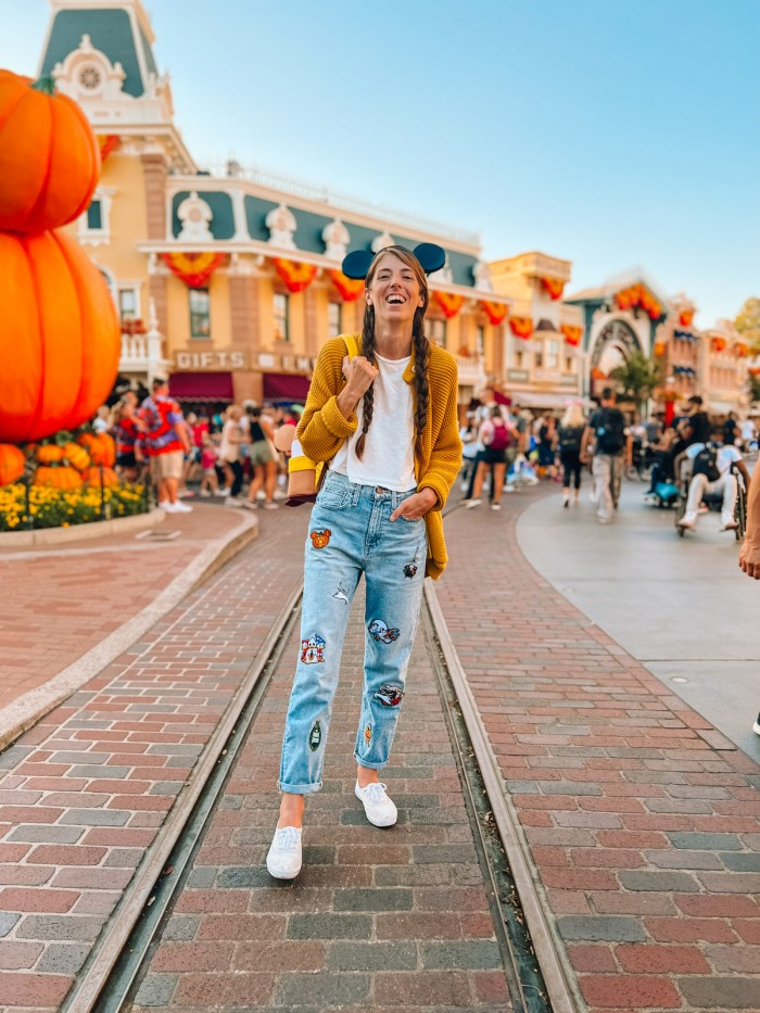 Woman in Disney patch jeans at Disneyland during Halloween