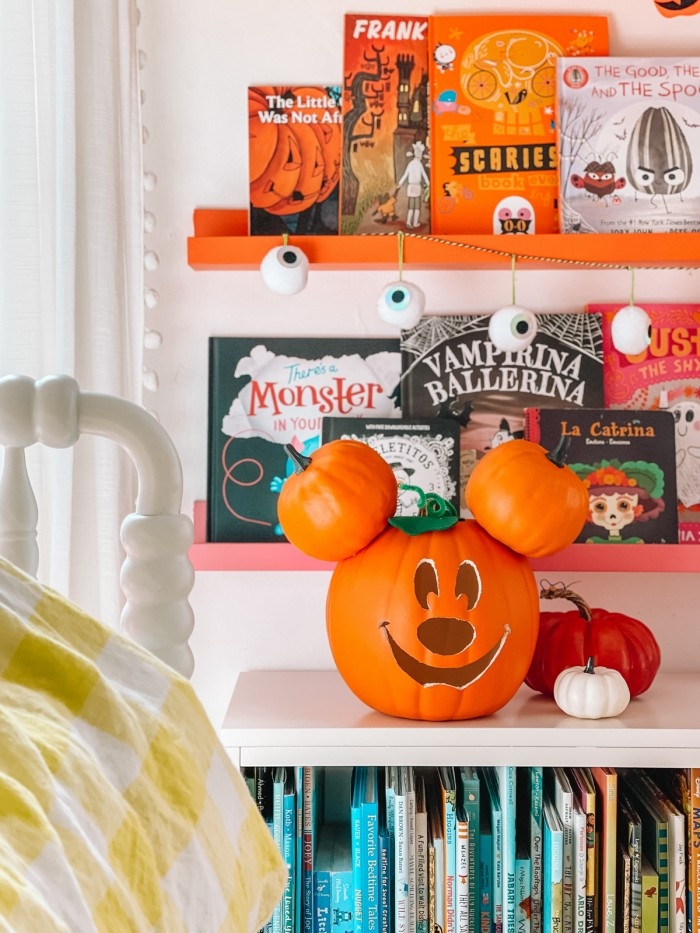 Mickey Mouse pumpkin in front of Halloween books and bookshelves next to bed