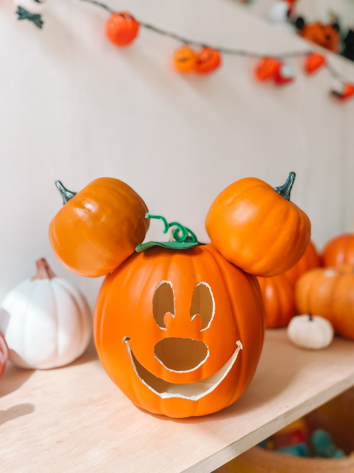 Mickey Pumpkin on shelf in front of pumpkins and white wall
