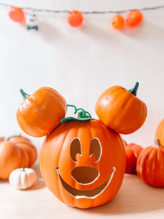 Mickey Mouse pumpkin in front of pumpkins, white wall and pumpkin lights