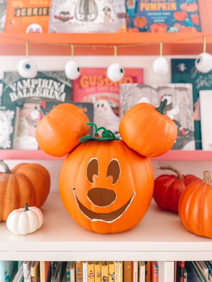 Mickey pumpkin in front of Halloween books and eye ball garland