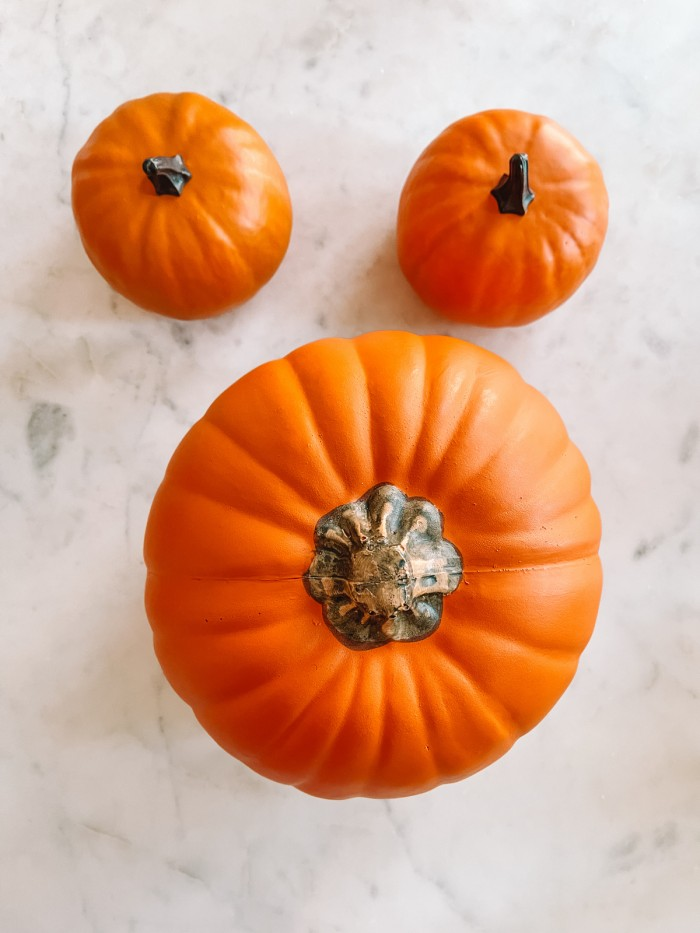 One large pumpkin with two small pumpkins above it on marble table