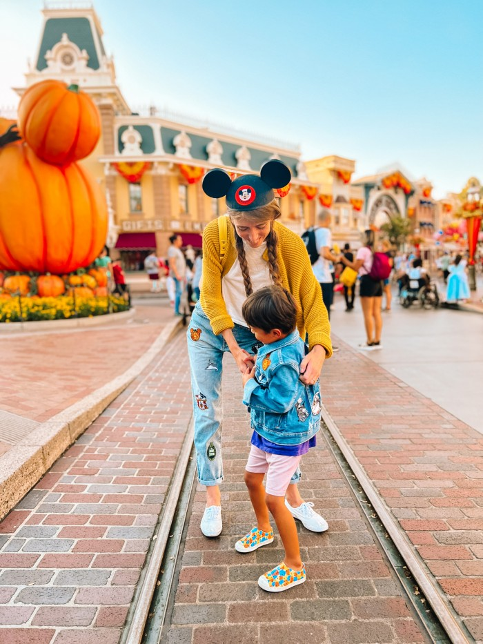 Mom and son on Main Street at Disneyland with Mickey Pumpkin behind them