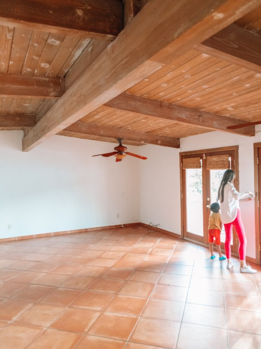 Mom and child in empty house with terracotta floors and wood beamed ceilings